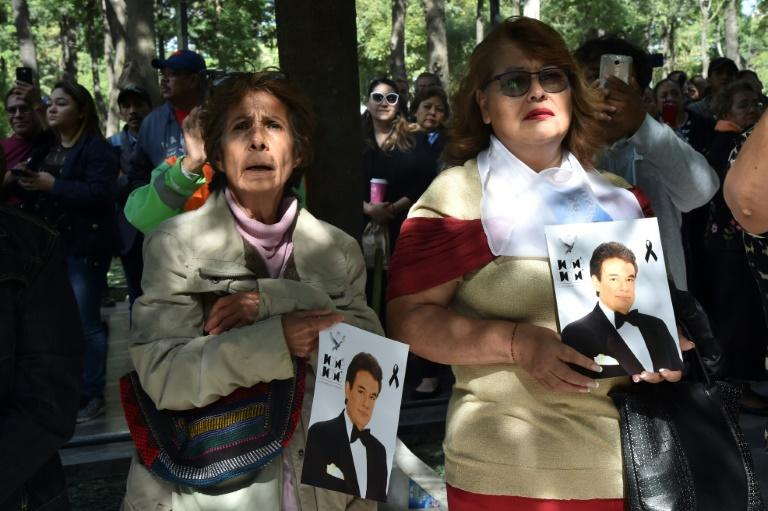 Fans pay tribute to late Mexican singing legend Jose Jose as the hearse carrying his remains heads to the Palace of Fine Arts in Mexico City (AFP Photo/RODRIGO ARANGUA                     )