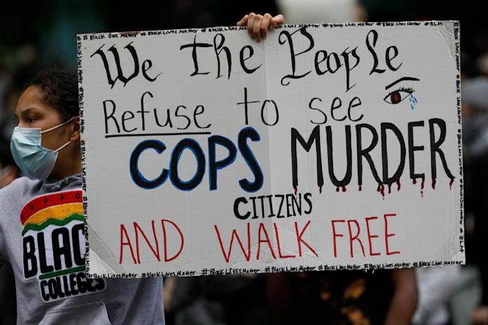 """<i>People carry a banner that says """"We the people refuse to see cops murder citizens and walk free"""" as they march to protest the death of George Floyd on May 31 in Portland, Oregon.</i>"""