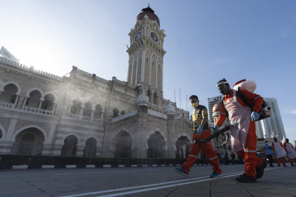 City hall workers spray a disinfectant at Merdeka Square, or independence square, situated in front of the Sultan Abdul Samad Building, background, in Kuala Lumpur, Malaysia, Saturday, Oct. 17, 2020. Malaysia will restrict movements in its biggest city Kuala Lumpur, neighboring Selangor state and the administrative capital of Putrajaya from Wednesday in an attempt to curb a sharp rise in coronavirus cases. (AP Photo/Vincent Thian)