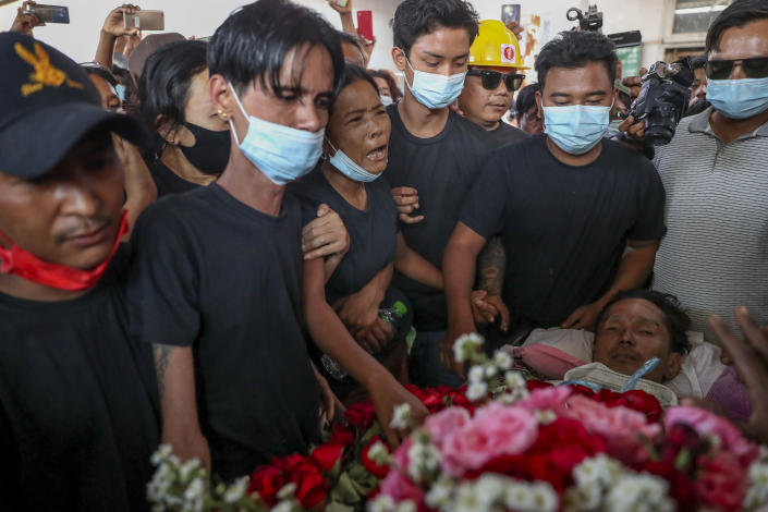 Thida Hnin, third from left, cries over the body of her husband Thet Naing Win during his funeral at Kyarnikan cemetery in Mandalay, Myanmar, Tuesday, Feb. 23, 2021. Thet Naing Win was shot and killed by Myanmar security forces during an anti-coup protest on Saturday, Feb. 20. (AP Photo)