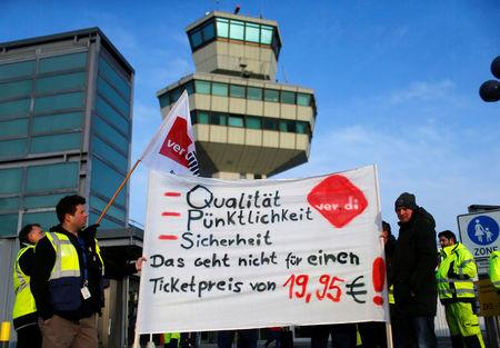 "Members of Germany's Verdi union protest with flags at a gate at Tegel airport during a warning strike by ground services, security inspection and check-in staff in Berlin, Germany March 13, 2017. Words read: ""Quality, Punctuality, Security - that's impossible with a ticket price of 19,95€!"". REUTERS/Hannibal Hanschke"