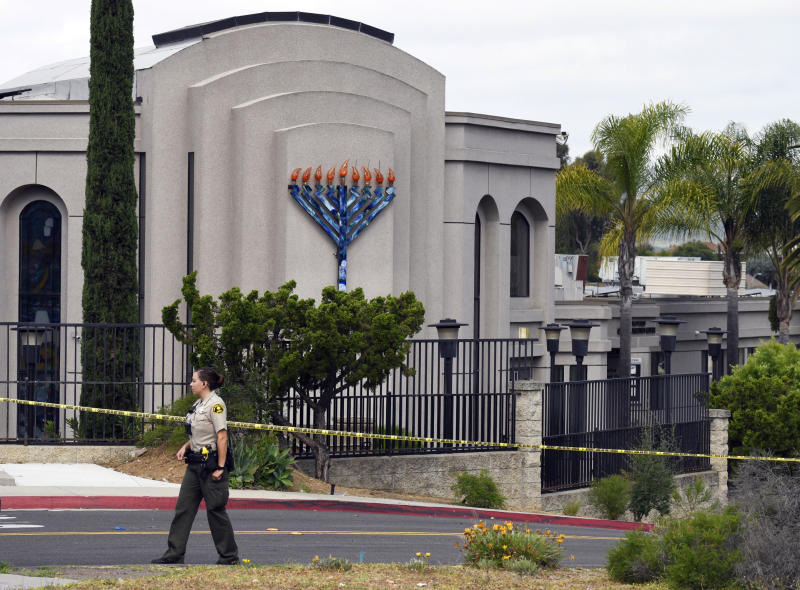 FILE - In this Sunday, April 28, 2019 file photo, a San Diego county sheriff's deputy stands in front of the Poway Chabad Synagogue in Poway, Calif. Prosecutors say John T. Earnest opened fire during a Passover service at the synagogue on April 27, killing one woman and injuring three people, including the rabbi. A preliminary hearing for Earnest begins Thursday, Sept. 18, 2019, in state court and is expected to last up to two days. (AP Photo/Denis Poroy, File)
