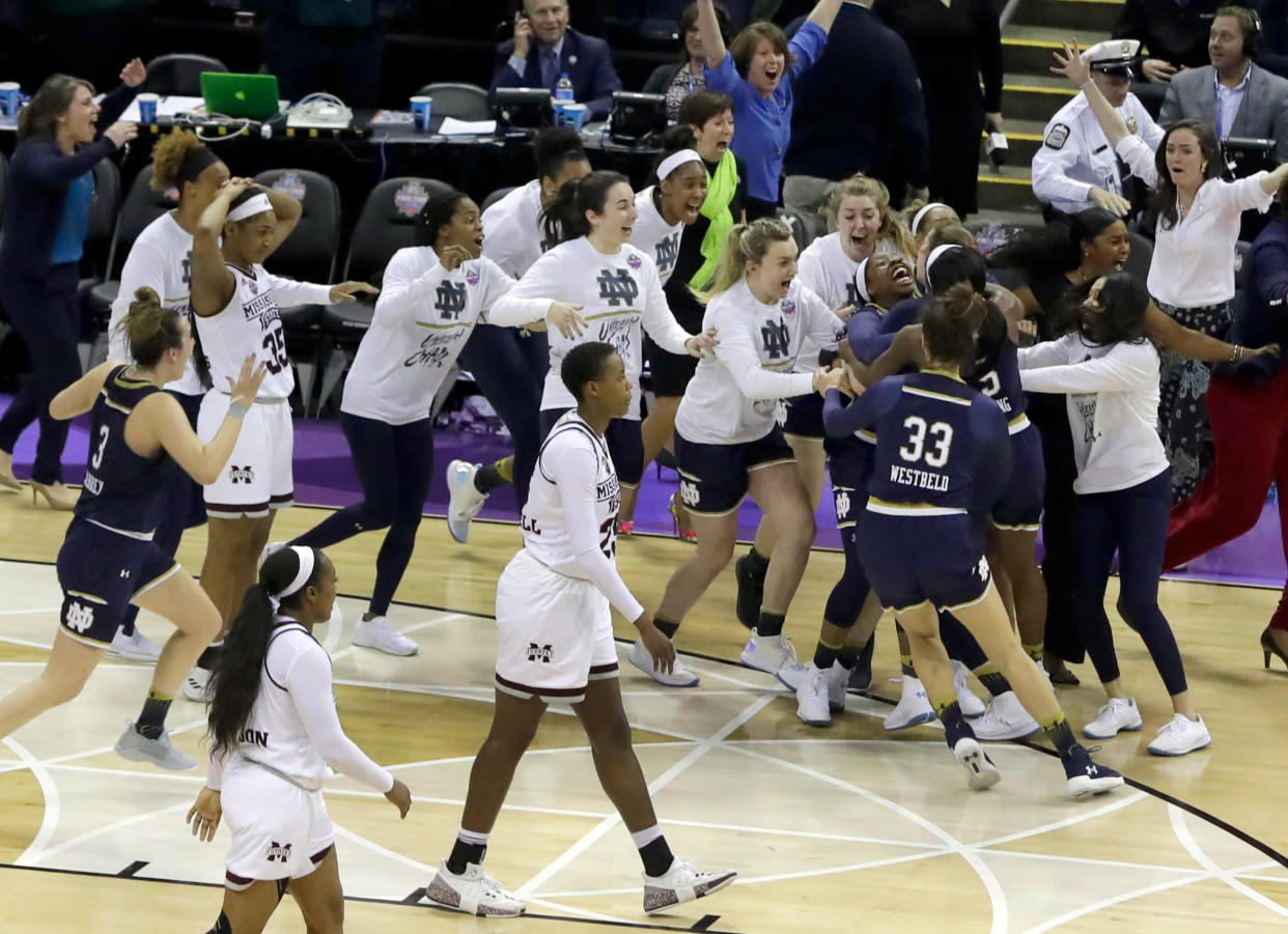 Notre Dame's Arike Ogunbowale is mobbed by teammates after sinking a 3-point basket to defeat Mississippi State 61-58 in the final of the women's NCAA Final Four college basketball tournament, Sunday, April 1, 2018, in Columbus, Ohio. (AP Photo/Tony Dejak)