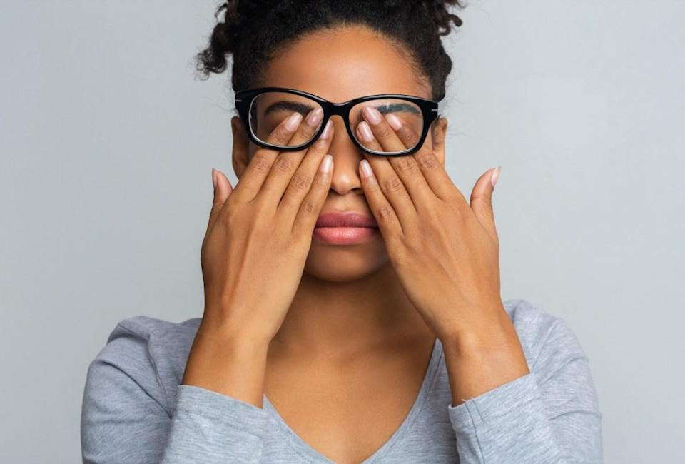 Woman in glasses rubs her eyes, suffering from tired eyes