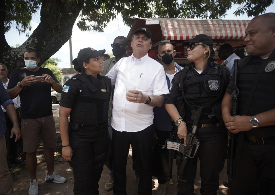 """Brazil's President Jair Bolsonaro, center, talks with police officers after voting during the run-off municipal elections in Rio de Janeiro, Brazil, Sunday, Nov. 29, 2020. Bolsonaro, who sometimes has embraced the label """"Trump of the Tropics,"""" said Sunday he'll wait a little longer before recognizing the U.S. election victory of Joe Biden, while also echoing President Donald Trump's allegations of irregularities in the U.S. vote. (AP Photo/Silvia Izquierdo)"""