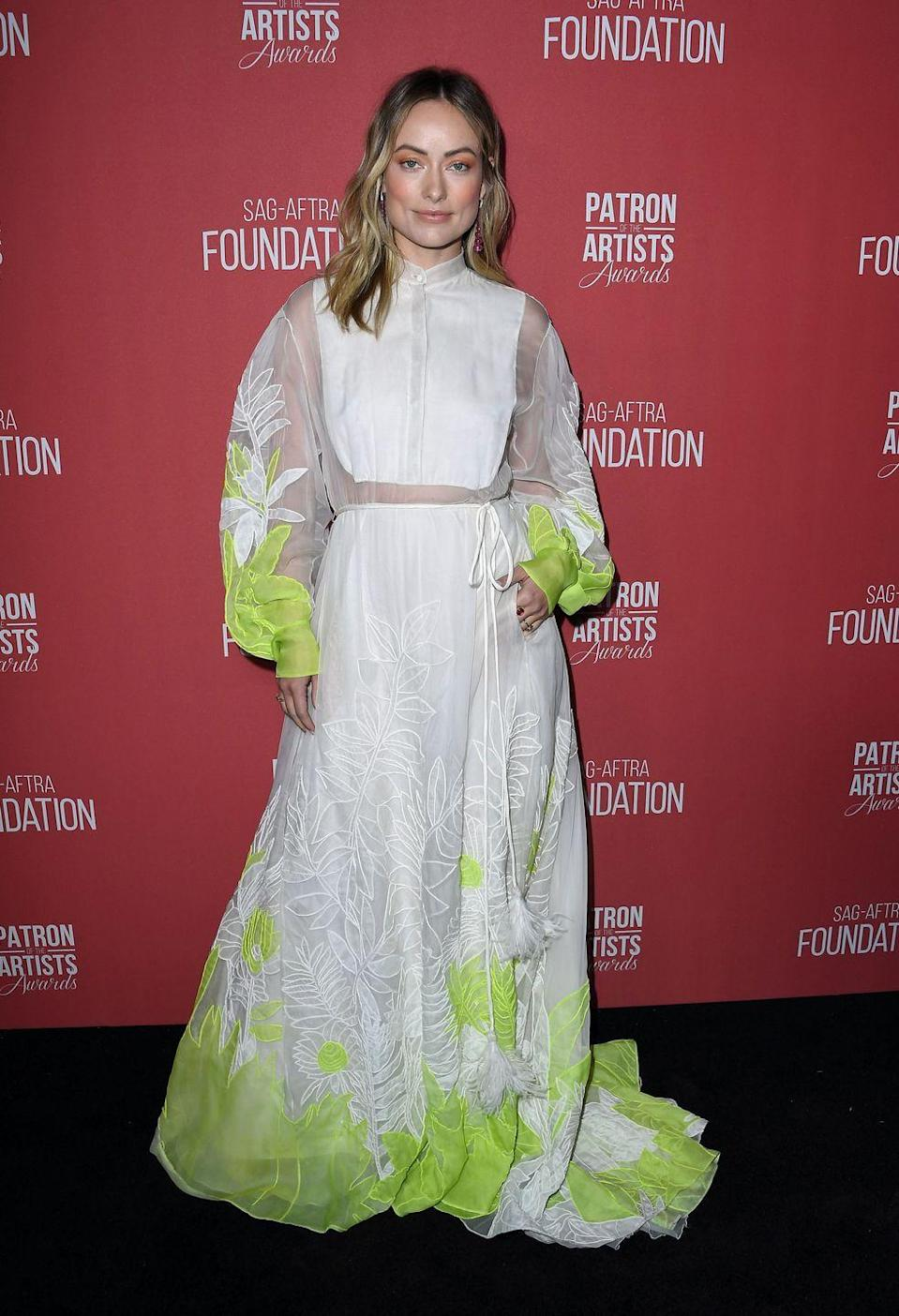 <p>Wilde wore a full-length white dress with see-through mesh sleeve and waistband accents and lime-green cuffs and hem. <br></p>