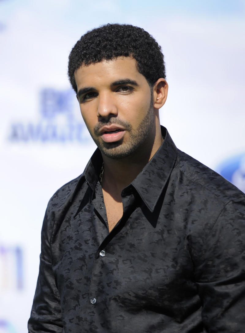 """FILE - In this June 26, 2011 file photo, Drake arrives at the BET Awards in Los Angeles. A day after earning his high school diploma, an excited Drake performed hit songs for a few hundred people at an event for Tyra Banks.  The 25-year-old told the crowd Thursday, Oct. 18, 2012, that he took a small break from music and """"spent some time going back to high school."""" He dropped out of high school, ironically, to star in the high school TV series """"Degrassi: The Next Generation.""""  (AP Photo/Chris Pizzello, file)"""