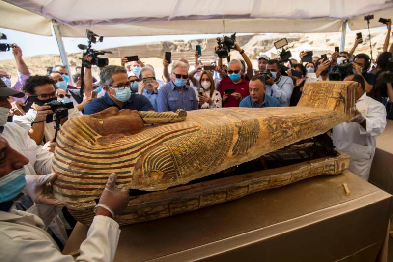 A picture taken on October 3, 2020 shows Egyptian Minister of Tourism and Antiquities Khaled Al-Anani (L), and Mustafa Waziri (R), Secretary General of the Supreme Council of Antiquities, open a sarcophagus excavated by the Egyptian archaeological mission working at the Saqqara necropolis, 30 kms south of the capital Cairo, which resulted in the discovery of a deep burial well with more than 59 human coffins closed for more than 2,500 years. - They were unearthed south of Cairo in the sprawling burial ground of Saqqara, the necropolis of the ancient Egyptian capital of Memphis, a UNESCO World Heritage site. Their exteriors are covered in intricate designs in vibrant colours as well as hieroglyphic pictorials. (Photo by Khaled DESOUKI / AFP) (Photo by KHALED DESOUKI/AFP via Getty Images)