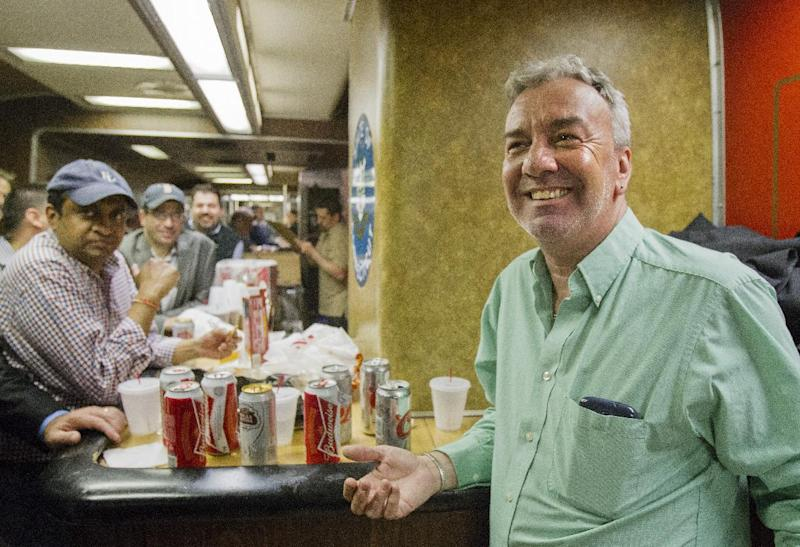 """Mark DeMonte, right, of Wallingford, Conn., join other riders in the bar car on the 7:07 p.m. train to New Haven, Conn., at Grand Central Terminal on Thursday, May 8, 2014 in New York. DeMonte, a bar car regular, has been dubbed """"Mayor of the 5:48"""" by friends and riders of his usual train. Metro-North is retiring bar cars from the New Haven Line after Friday's afternoon rush hour. They were the last commuter bar cars in the U.S. (AP Photo/Michael R. Sisak)"""