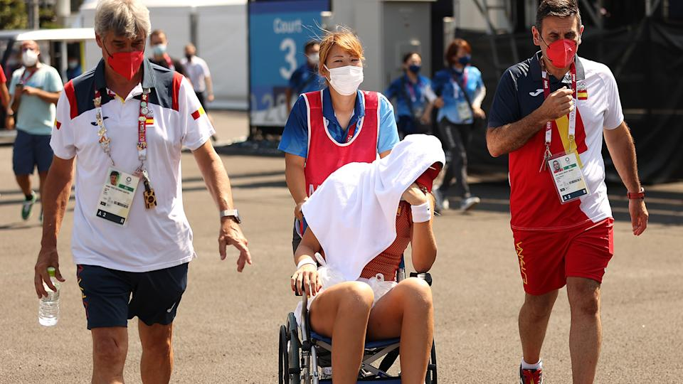 Paula Badosa of Team Spain is helped away from the court in a wheelchair due to heat stroke. (Photo by David Ramos/Getty Images)