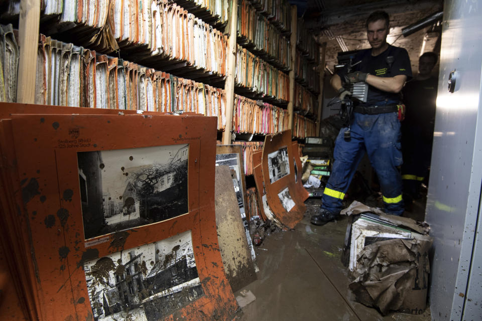 A helper of the Federal Agency for Technical Relief (THW) walks through the flooded city archive in Stolberg, western Germany, Sunday, July 18, 2021. Heavy rains caused mudslides and flooding in the western part of Germany. Multiple have died and are missing as severe flooding in Germany turned streams and streets into raging, debris-filled torrents that swept away cars and toppled houses. (Marius Becker/dpa via AP)