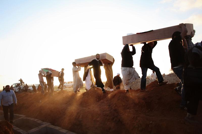 Libyan men carry coffins of victims, discovered in a mass grave, at a funeral in Benghazi, Libya, Monday, March 5, 2012. Thousands of mourners gathered Monday in the eastern Libyan city of Benghazi to bury 155 bodies unearthed from a mass grave of people were killed during last year's civil war. It was the largest grave yet to be discovered from the conflict that began as a popular uprising and ended with the capture and killing of Libyan leader Moammar Gadhafi last October.(AP Photo/Manu Brabo)