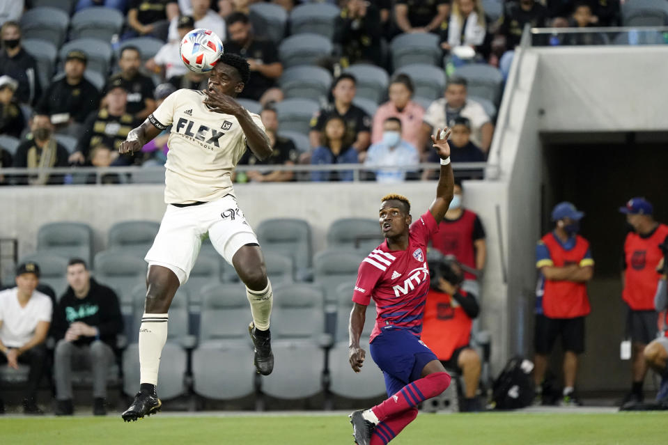 Los Angeles FC defender Jesus Murillo, left, heads the ball over Dallas FC forward Jader Obrian during the first half of an MLS soccer match Wednesday, June 23, 2021, in Los Angeles. (AP Photo/Marcio Jose Sanchez)