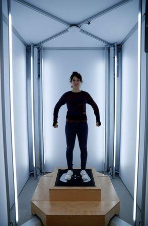 A staff member uses a laser body scanner to measure a customer's size before the individual knitting of a sweater at the Adidas Knit for You store in Berlin