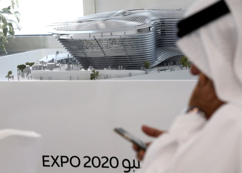 FILE PHOTO: A man uses his mobile device next to a model of the Expo 2020 project in Dubai, United Arab Emirates