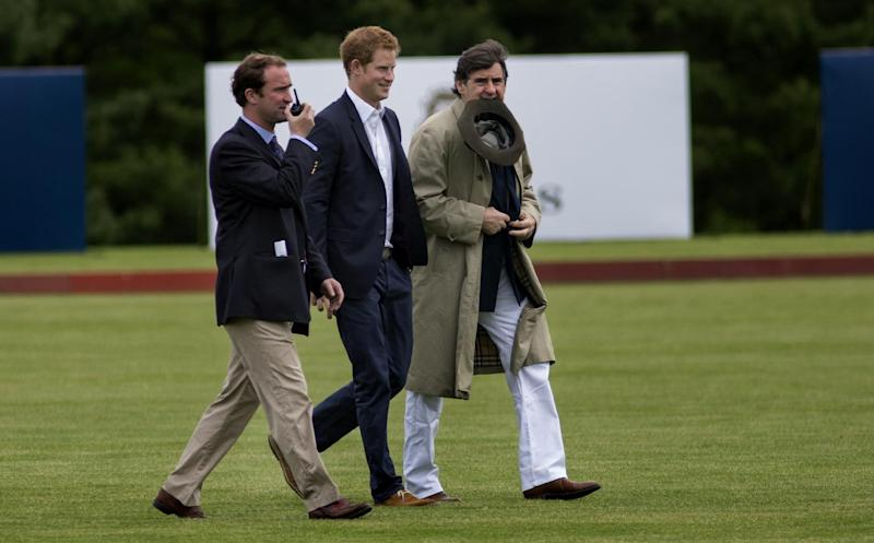 Britain's Prince Harry walks across the polo field before the Sentebale Royal Salute Polo Cup charity match in Greenwich, Conn., Wednesday, May 15, 2013. Right is Peter Brant, founder of the Greenwich Polo Club. (AP Photo/Craig Ruttle)