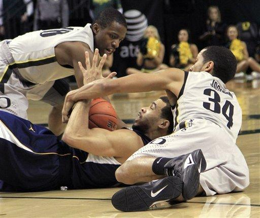 California guard Justin Cobbs, middle, vies for a loose ball with Oregon's Devoe Johnson, right, and Johnathan Loyd during the first half of an NCAA college basketball game in Eugene, Ore., Sunday, Jan. 8, 2012. (AP Photo/Don Ryan)