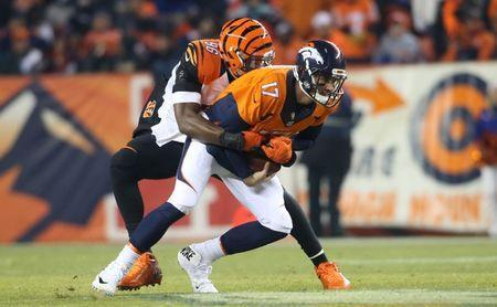 Dec 28, 2015; Denver, CO, USA; Denver Broncos quarterback Brock Osweiler (17) is sacked by Cincinnati Bengals defensive end Carlos Dunlap (96) during the first half at Sports Authority Field at Mile High. Mandatory Credit: Chris Humphreys-USA TODAY Sports / Reuters Picture Supplied by Action Images