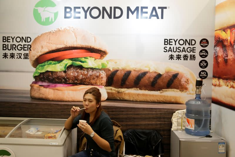 A woman sits next to a poster at the booth of plant-based food company Beyond Meat at VeggieWorld fair in Beijing