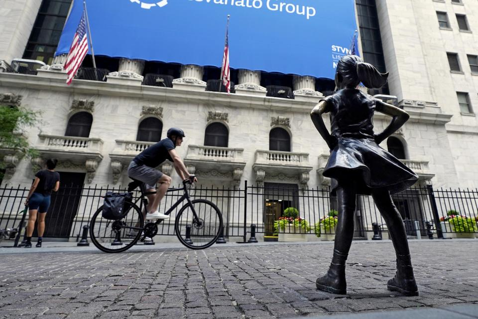 FILE - The Fearless Girl statue faces the New York Stock Exchange, Tuesday, July 20, 2021. Stocks are off to a mixed start on Wall Street, Friday, Aug. 13 as gains for communications and health care companies are checked by weakness in energy and other sectors.  (AP Photo/Richard Drew)