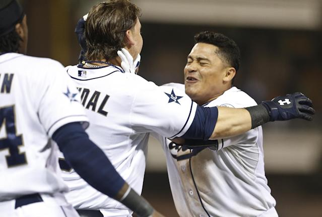 San Diego Padres' Everth Cabrera, right, is swarmed by teammates after his sacrifice fly drove in the winning run in the ninth inning of the Padres' 6-5 victory over the Los Angeles Dodgers in a baseball game Friday, June 20, 2014, in San Diego. (AP Photo/Lenny Ignelzi)