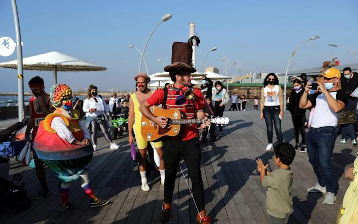 Actors in costumes perform to people during the Purim holiday celebrations in the port of Tel Aviv - Shutterstock