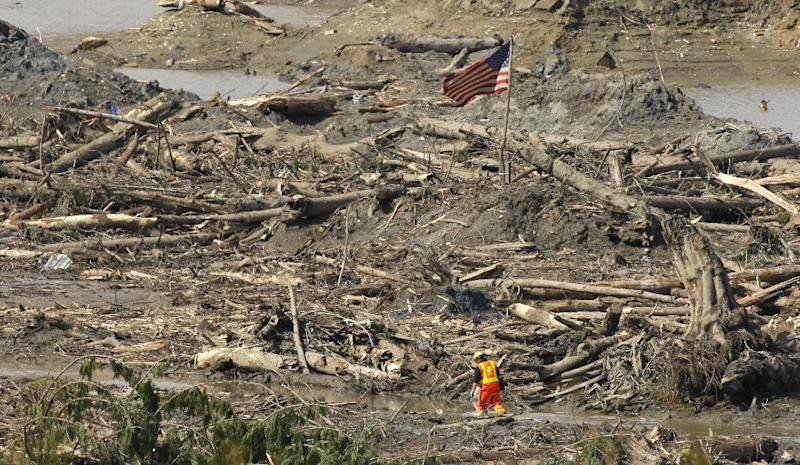 A searcher walks through a channel of water as a flag flies in the debris field Monday, March 31, 2014, near Darrington, Wash., at the site of the massive mudslide that hit the nearby community of Oso,Wash. on March 22, 2014. (AP Photo/Ted S. Warren)
