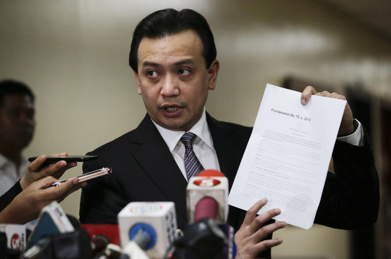 Philippine opposition Sen. Antonio Trillanes IV shows to reporters a copy of his amnesty documents outside his office where he remains holed up in the Philippine Senate in suburban Pasay city, south of Manila, Philippines on Tuesday, Sept. 11, 2018. Trillanes has been staying inside his senate office for over a week to avoid an arrest order by Philippine President Rodrigo Duterte. (AP Photo/Aaron Favila)