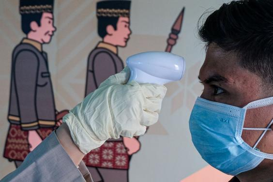 A person checks the temperature of a passenger wearing a facemask as he arrives at the Sultan Mahmud Badaruddin II International airport in Palembang (AFP via Getty Images)