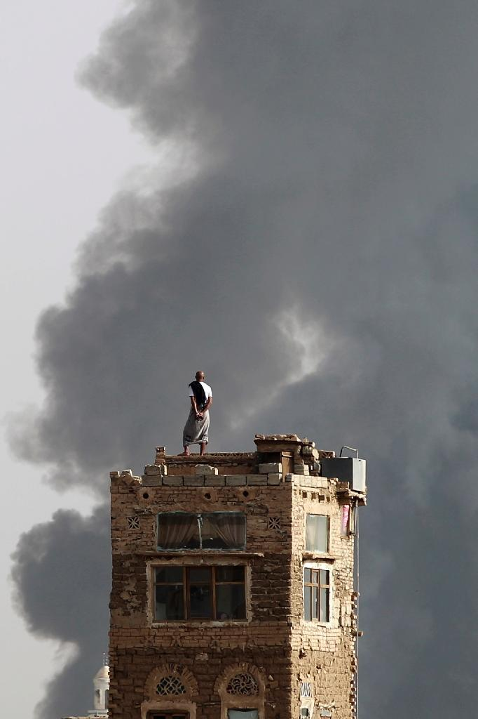 A Yemeni man standing on the roof of a house watches billowing smoke after an air-strike by the Saudi-led coalition on a weapons depot at a military airport, currently controlled by Yemeni Shiite Huthi rebels, on July 7, 2015 in Sanaa (AFP Photo/Mohammes Huwais)
