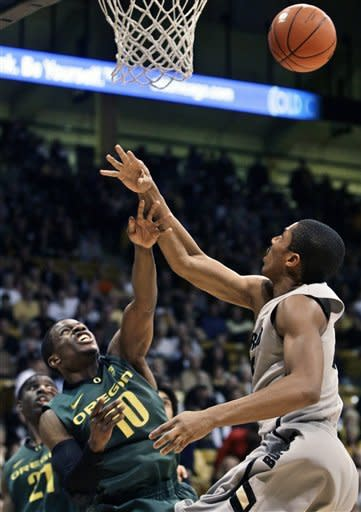 Colorado's Spencer Dinwiddie, right, blocks a shot by Oregon's Johnathan Loyd during the first half of an NCAA college basketball game in Boulder, Colo., Thursday, March 7, 2013. (AP Photo/Brennan Linsley)