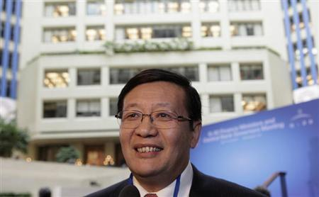 Chinese Minister of Finance Lou smiles before G20 finance ministers and central bank governors family photo in Washington