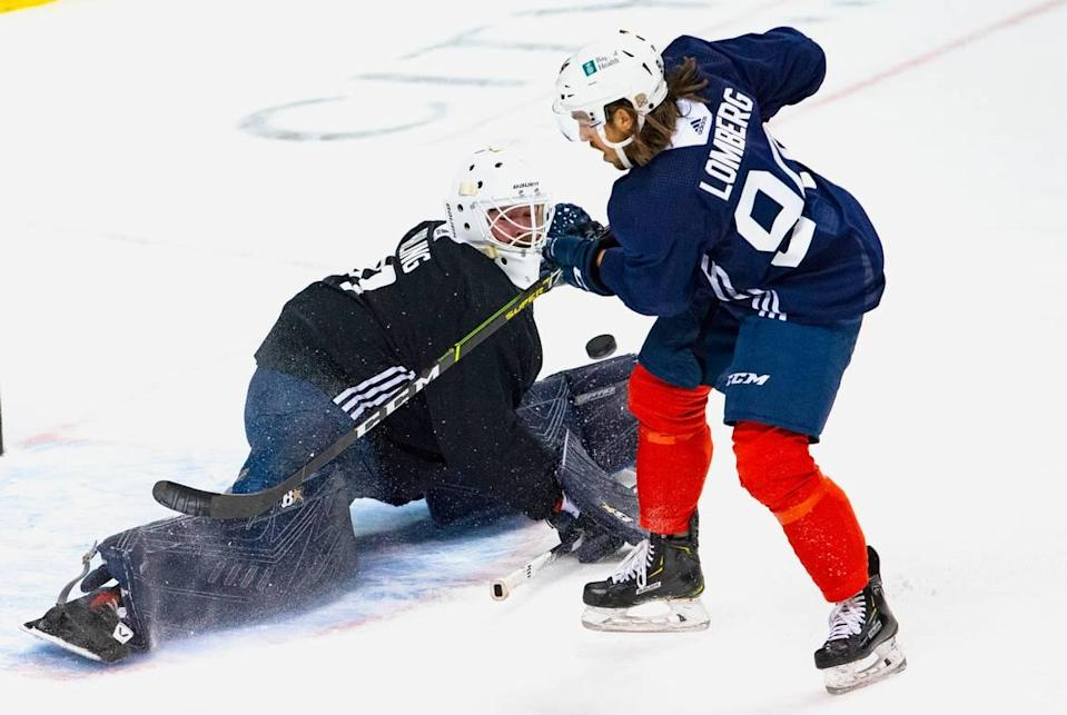 Florida Panthers goalie Scott Darling (31) blocks a shot by Florida Panthers left wing Ryan Lomberg (94) during the first practice of training camp in preparation for the 2020-21 NHL season at the BB&T Center on Monday, January 4, 2021 in Sunrise.