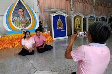 Well-wishers wear pink shirts as they pose for a photograph in front of a picture of Thailand's King Bhumibol Adulyadej at Siriraj Hospital in Bangkok, Thailand, October 11, 2016. REUTERS/Chaiwat Subprasom
