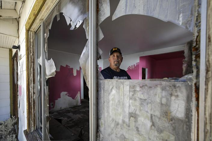 A man stands inside an abandoned home with shattered windows