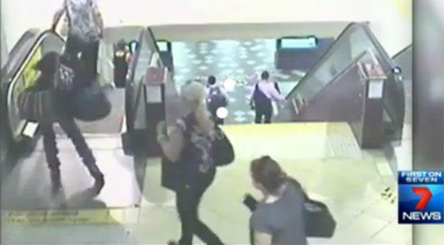 This guy with with bags is moments from toppling over on the escalator. Photo: 7 News