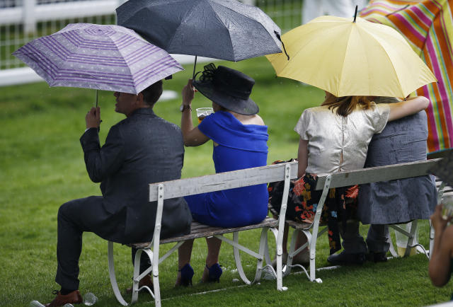 Britain Horse Racing - Derby Festival - Epsom Racecourse - June 2, 2017 Racegoers use umbrellas to shield themselves from the rain Reuters / Peter Nicholls Livepic EDITORIAL USE ONLY.