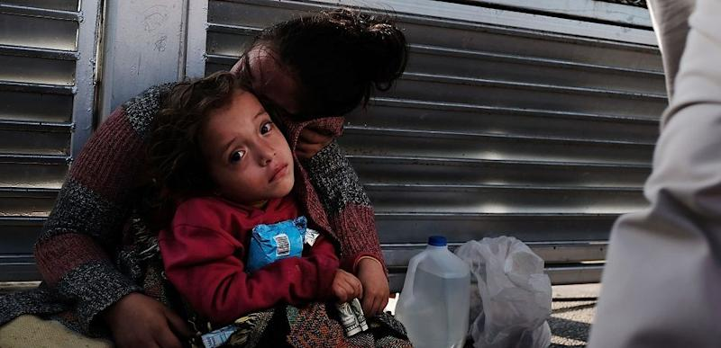 A Honduran child and her mother, fleeing poverty and violence in their home country, wait along the border bridge after being denied entry into the U.S.