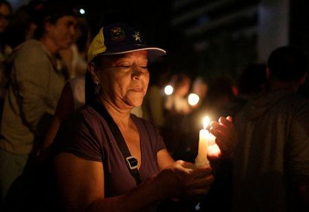 Opposition supporters hold candles while participating in a candlelight rally against President Nicolas Maduro in Caracas, Venezuela, May 17, 2017. REUTERS/Marco Bello