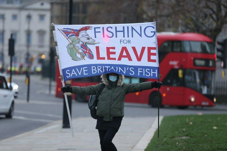 Protester holding sign 'Fishing for Leave'