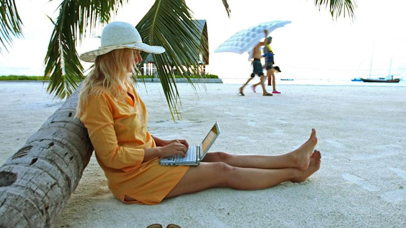 Woman sitting on Villingili beach working with a notebook and mobile phone in Male, Maldives. (Photo by EyesWideOpen/Getty Images)