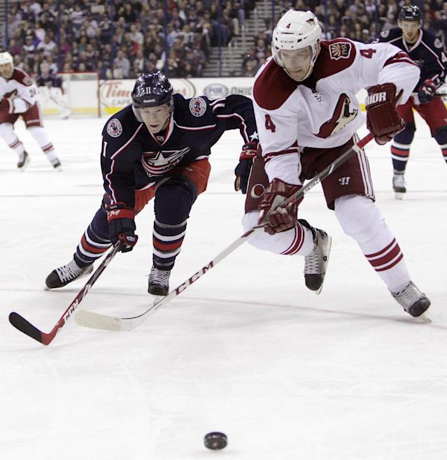 Phoenix Coyotes' Zbynek Michalek, right, of the Czech Republic, and Columbus Blue Jackets' Matt Calvert chase a loose puck during the second period of an NHL hockey game Tuesday, April 8, 2014, in Columbus, Ohio. (AP Photo/Jay LaPrete)