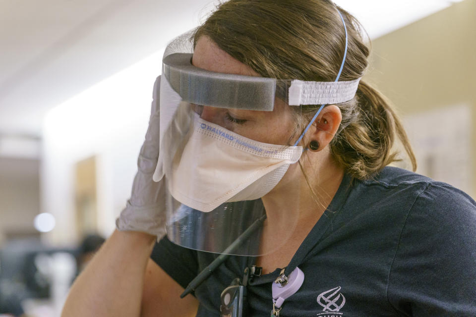 Emily Williams, a registered nurse on one of the intensive care units at Oregon Health and Science University in Portland, Ore., wipes down her face shield with disinfectant, Thursday, Aug. 19, 2021. OHSU has four intensive care units, including a 16-bed medical ICU that has been converted into a unit dedicated to COVID-19 patients. (Kristyna Wentz-Graff/Pool Photo via AP)
