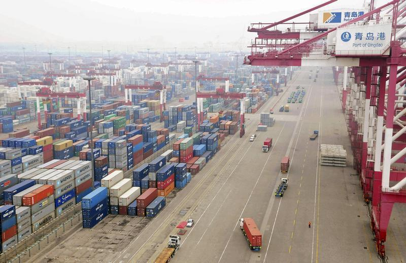 Trucks are used to transport containers at a port in Qingdao, Shandong province