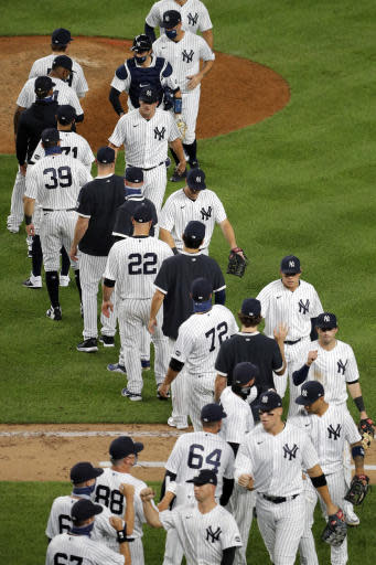 The New York Yankees celebrate after the baseball game against the Boston Red Sox at Yankee Stadium, Friday, July 31, 2020, in New York. The Yankees defeated the Red Sox 5-1. (AP Photo/Seth Wenig)