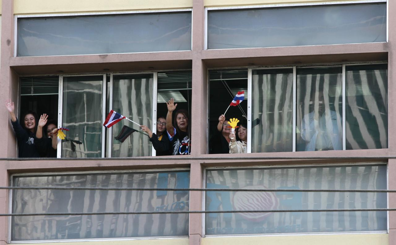 Thai workers wave Thai national flags from a window as anti-government protesters march in a rally in Bangkok January 21, 2014. Some Thai rice farmers have threatened to switch sides and join protesters trying to topple the government if they do not get paid for their crop, a worrying development for Prime Minister Yingluck Shinawatra whose support is based on the rural vote. REUTERS/Chaiwat Subprasom (THAILAND - Tags: POLITICS CIVIL UNREST)