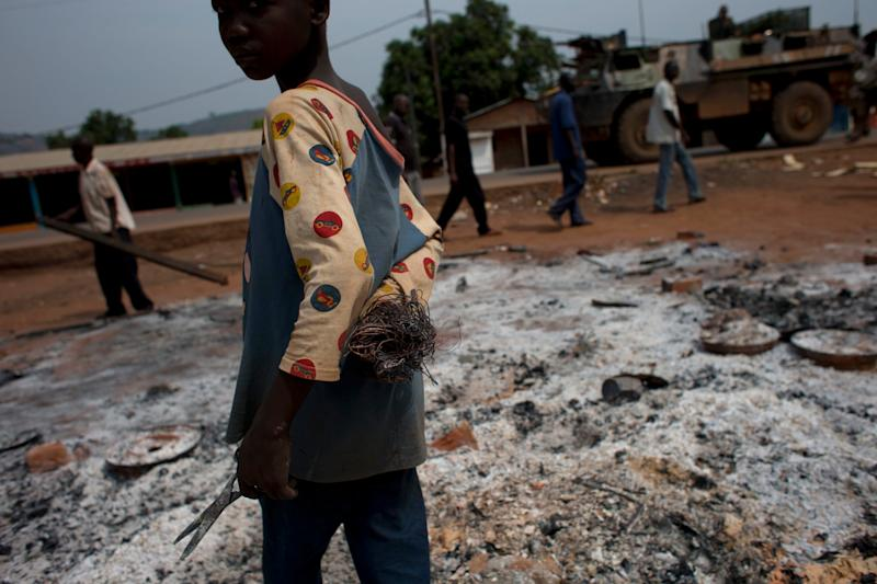A boy salvages scraps of metal from the remains of burned shops, as French soldiers stand guard in a neighborhood where Chadian soldiers clashed with anti-balaka Christian militiamen on Wednesday afternoon, in the Gobongo neighborhood of Bangui, Central African Republic, Thursday, Dec. 26, 2013. The spokesman for an African Union peacekeeping force says six Chadian peacekeepers were killed and 15 were wounded, after being attacked Wednesday. The Chadian contingent, which is made up of Arabic-speaking Muslim soldiers, has been accused of taking sides against the Christian population in the country's sectarian conflict. (AP Photo/Rebecca Blackwell)