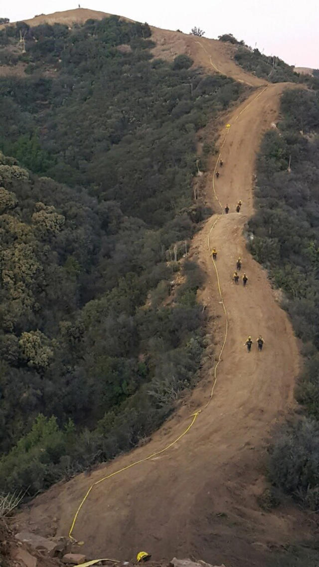 <p>Firemen clear a fire break and lay ten thousand feet of hose across a canyon from atop Camino Cielo down to Gibraltar to make a stand should the fire move in that direction Wednesday Dec. 13, 2017, in the Santa Ynez Mountains area of Santa Barbara, Calif. (Photo: Mike Eliason/Santa Barbara County Fire Department via AP) </p>