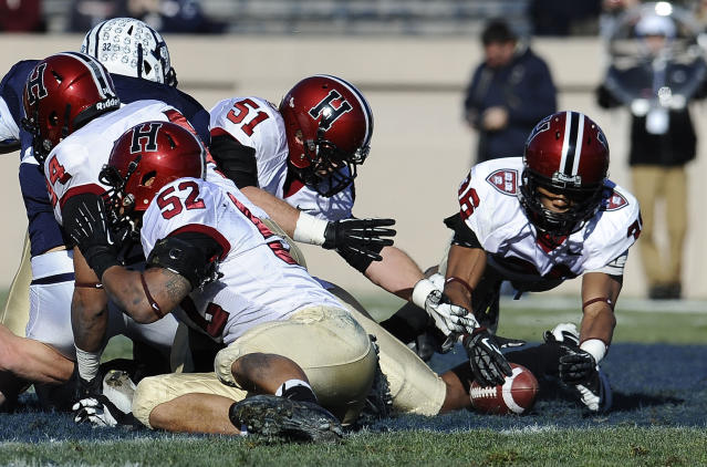 Harvard defensive back D.J. Monroe (36), right, reaches for a fumble made by Yale wide receiver Candler Rich (32), rear left, during the first half of an NCAA college football game at Yale Bowl, Saturday, Nov. 23, 2013 in New Haven, Conn. (AP Photo/Jessica Hill)