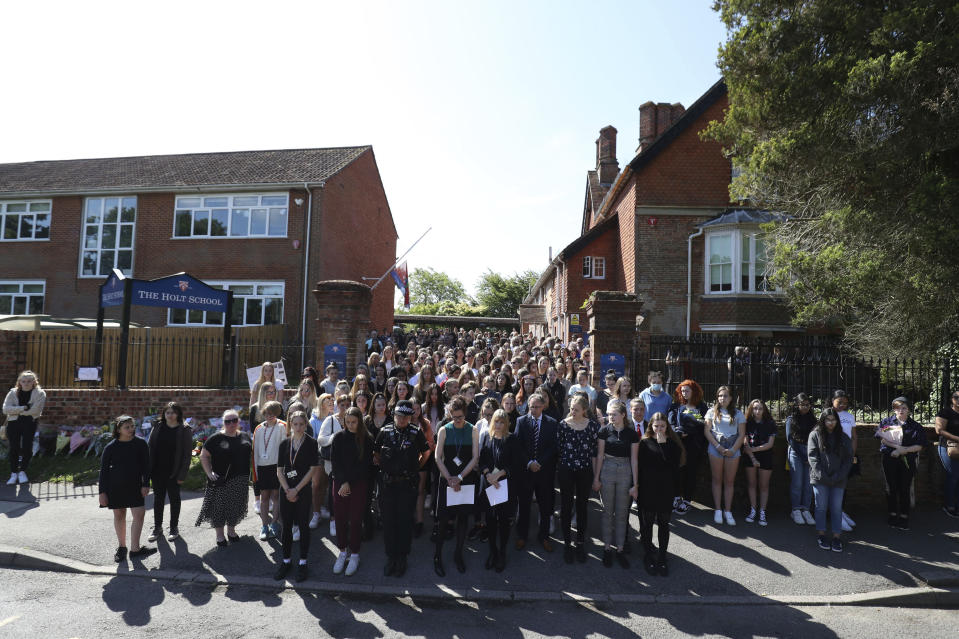 Colleagues and pupils of teacher James Furlong stand together to take part in a period of silence at the Holt School, in Wokingham, England, in memory of teacher James Furlong, a victim of a terror attack in nearby Reading, Monday June 22, 2020.  A lone terror suspect remains in custody accused of killing three people and wounding three others in a Reading park on Saturday night. (Steve Parsons/PA via AP)